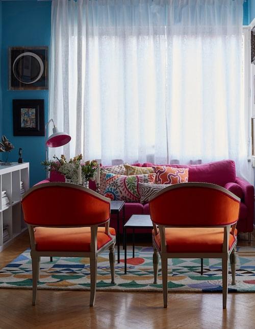 Vardagsrummets väggar är fyllda av konst från olika tidsperioder, uppsatta på ett okonventionellt sätt. De gustavianska baljfåtöljerna från 1700-talet är läckert omklädda i stark orange med lilafärgade passpoaler. Mattan är ritad av Josef Frank och producerad av Designbrenner.