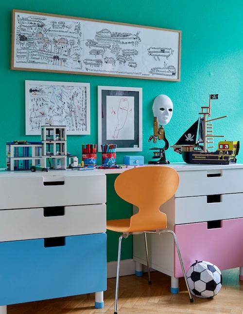 I sonen Abbes rum hänger hans egna alster över skrivbordet från Ikea. Myranstol i knallorange.