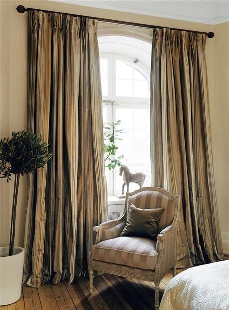 De fylliga sovrumsgardinerna i dova toner hänger fritt utan omtag, på så sätt blir intrycket maskulint, elegant och avslappnat.