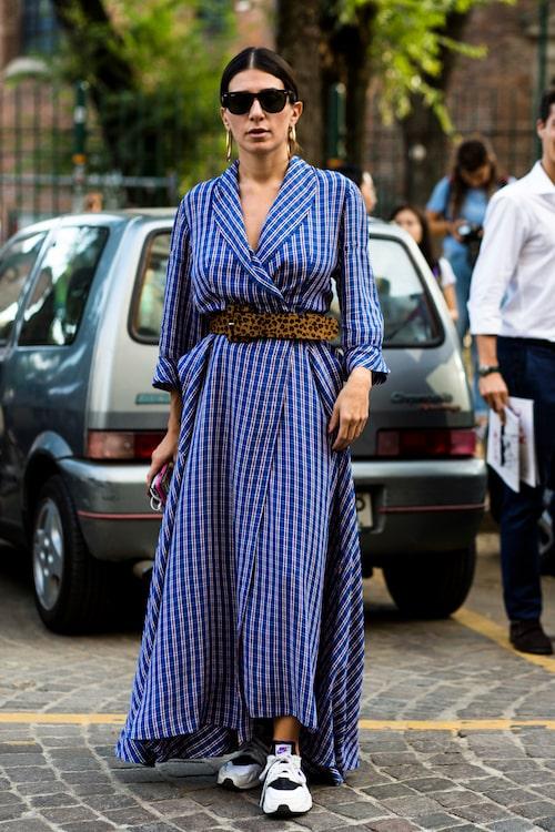 Matcha en rutig klänning med skärp och sneakers för en stilsäker helhet.