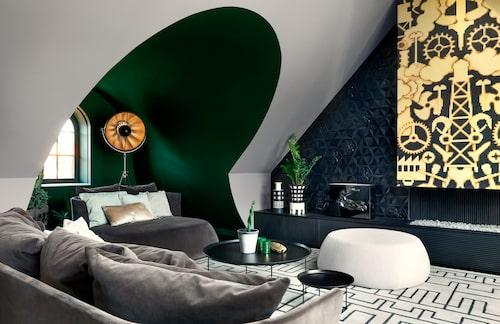 """Från vitt till svart: Före makeovern var detta rum vitt. För Harry Granlund, Gecos inredningsarkitekt, var det snudd på helgerån att inte förhöja den arkitektoniska dramatiken med färg. Fönsternischen målades i mörk grönsvart umbra, och taket i en ljusare umbra, från KT color. Kortväggen blev ett konstverk när öppna spisen täcktes av guld–svart mosaik, av Studio Job för Bisazza, och svart kakel av Marcel Wanders, Bisazza. """"Vilka grejer är spännande i ett rum? Förstärk dem med färg! För lite djungelfeeling förde jag också in växter."""" Ljus saknas inte, hela den motstående väggen är glasad ut mot terrassen i öster. Fotolampan med bladguldinvändigt är från Venetia studiums Fortuny-serie. Mullvadsfärgad sammetssoffa och divan Fat, samt brickbord, BB Italia, keramikvaser Ettore Sottsass. Tibetansk handtuftad matta, från Geco."""