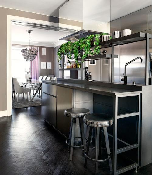 """Proffskök: Köket är Patricia Urquiolas Salinas för Bof . De matt grafitgrå luckorna har så kallad paper stone finish. """"Köksöns sida närmast, är för matlagning, och den bortre, för disk. Jag gillar skarpt att ön också har hyllor att ställa saker på. I det här köket ska det lagas mat, så alla vitvaror är proffsmaskiner från Grande cuisine."""" I den angränsande matsalen: silkes- matta med blomstermotiv, och takkrona, Brand van Egmond."""