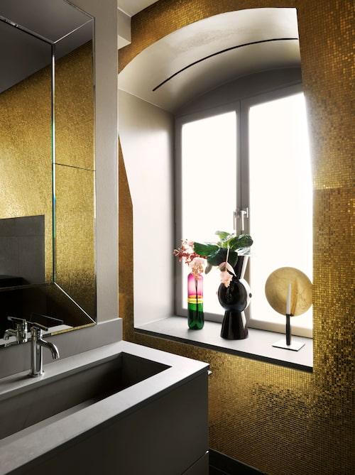 Guldläge: Materialen är italiensk kalksten och mosaik från Bisazza. Badrumset från Bof  och spegel slipad i venetiansk stil, hämtad av Harry i Venedig. Kulört vas, Venini, ljusstake, Catellani & Smith.