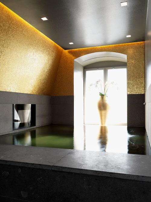 """Romerskt bad med tv: """"Vi ville skapa en varm, lustfylld stämning av både romerskt bad och modernt spa."""" Ja, det som är infällt i kalkstensväggen är en tv-skärm. Vas från B&B Italia."""