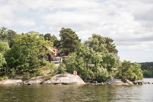 Röda villan på Fjäderholmarna är ett skärgårdshus från 1897 som byggts om till restaurang med grill, kafé och bar. Nere vid vattnet finns hängmattor där gästerna kan ta sig en tupplur.