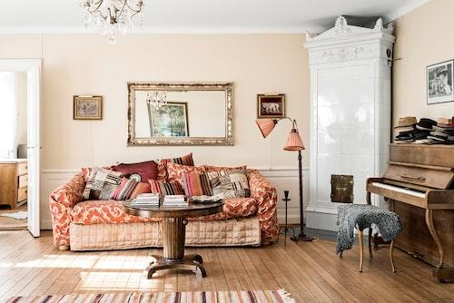 """""""Jag kan inte sitta i en soffa utan lägger mig alltid ner, även hemma hos vänner."""" Vardagsrummet är stort och här tronar favoritmöbeln, en Cadillac-soffa från gamla House. På pianot, som liksom det mesta är arvegods, samlar Bosse sina hattar."""