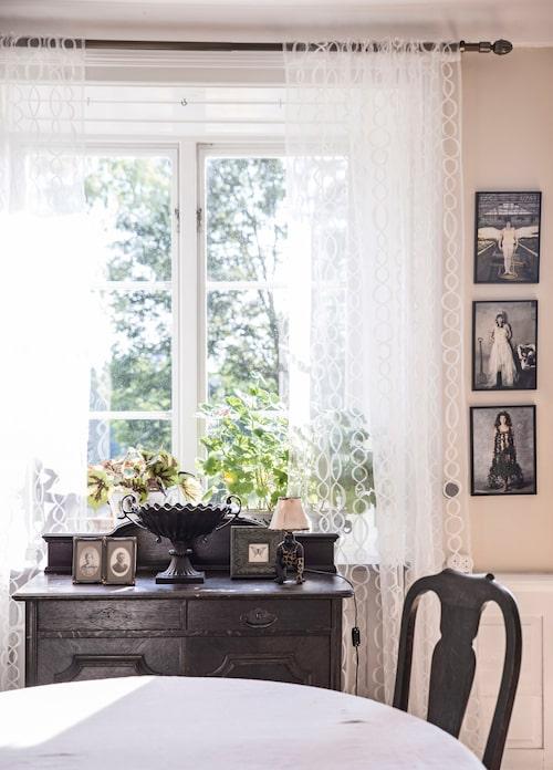 Skänken i jugendstil är en del av den stora matsalsmöbeln och kom med huset. Fotografierna kommer från konstprojektet Kejsarens nya kläder som Bosse gjorde med konstnären Monica Lundegård.