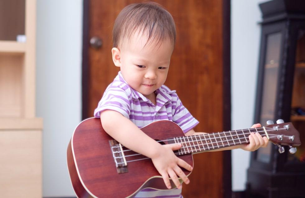 Mamma spelar gitarr, då gör jag det också … Små barn lär sig förstå sin kultur genom att härma. (Barnet på bilden har inget samband med texten) Foto: Shutterstock