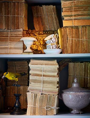 Böckerna man läser finns på övervåningen, där också tv:n placerats. I biblioteket däremot får gamla luntor ge karaktär. Bergèren från tidigt 1800-tal, klädd i ett handmålat linnetyg, är en av två likadana läsfåtöljer som flitigt används. I köket hänger nytillverkade rokokostolar på shakervis, lätta att lyfta ned när man får gäster.
