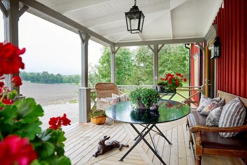 Två planteringsbord i järn har sin plats på den nybyggda verandan. Stommen, liksom fönsterfoder, är målade i en lergrön nyans, fasaden i falurött och spröjsen i ockra.