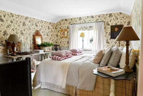 """Sovrummet på övervåningen är inbäddat i tapetens mjuka växtlighet; samma motiv, Pillemont toile, återkommer i hissgardinen, från Sanderson. Tapetens milda framtoning kontrasteras av lila i kuddar och lampskärmar, och sängklädernas ränder och rutor. Som nattduksbord används två antika pelarbord, på det grova bockbordet ryms några av Jims och Alexanders många """"besjälade"""" föremål."""
