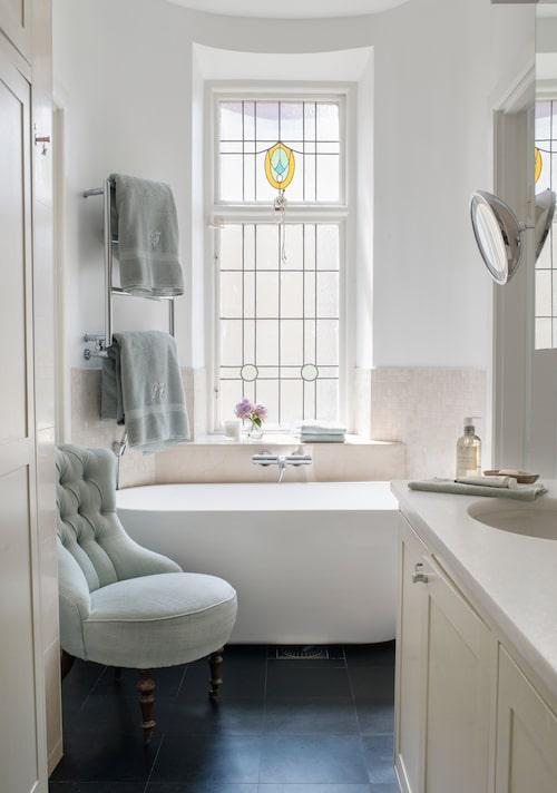 Föräldrarnas badrum fräschades upp med bland annat ny färg på väggar och skåp, ny marmorskiva och nytt badkar. Emmafåtölj med tyg från Larsen/ Cadoro.