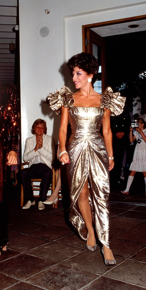 Joan Collins i en Nolan Millerkreation 1985. I bakgrunden: den svenske sångaren Peter Holm som var gift med Joan.