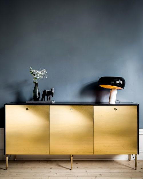 Ett sideboard med guldfronter och svart granitskiva kostar ca 25 000 kronor.