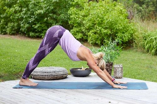 Yogaövningen Stående hunden stärker fot- hoch handleder samt ökar blodcirkulationen.