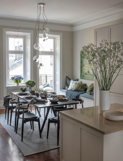 Vid köksön kan man också duka upp till en måltid. Taklampa från kanadensiska Bocci.