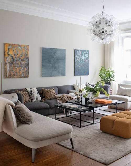 """I det luftiga vardagsrummet får hela familjen plats i soffan, som är 4,25 meter lång. """"Det är små orange trådar i det grå, som vi plockade upp i puffen."""" Soffa, Fogia Retreat, divan och sittpuff från B&B Italia, bord och fåtöljer, Slettvoll, lampa Perch lamp, Moooi, matta, Layered, kuddar, Posh living, plädar, Mantas Ezcaray."""