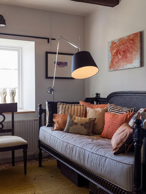 I arbetsrummet går de ockrafärgade accenttonerna över till korall i soffan från Ballard Designs. Den vackra samlingen kuddar lyses upp av Tolomeo Mega från Artemide.