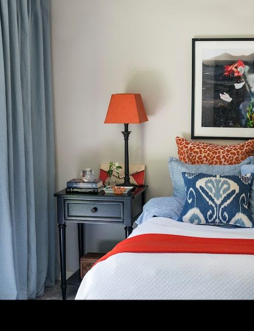 Sovrummet ligger på bottenvåningen i souterränghuset med utgång mot trädgård. En härlig färgkombination av ljusblått och orangerött mot vitt – lampskärmarna fick ange tonen för den övriga inredningen – ger en ombonad känsla. Ikatmönstrad kudde sydd av Cecilia med tyg från Walles & Walles. Ljushållare Ludvig Löfgren för Kosta Boda.