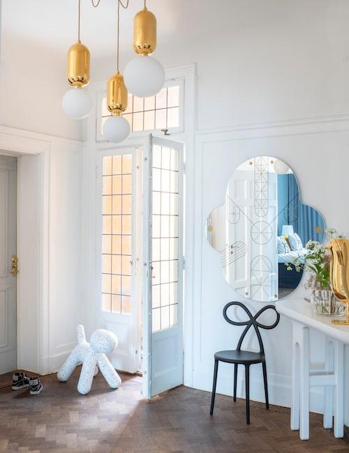 Fiskbensparketten är slipad och lackad i en valnötsbrun färg för att skapa värme  i lägenheten. I hallen står en skänk som Jaime Hayon gjorde till Lindas tidigare affär, han har även designat spegeln King Kong och taklamporna Aballs. Ribbon chair av Nica Zupanc och dalmatinerhund från Magis.