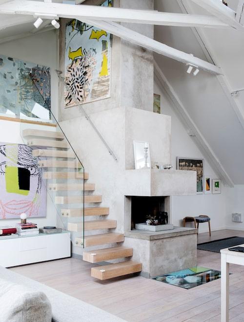 Trivsam betong i vardagsrummet. Sidobord från Arctic, målningen ovanför är av Bjarne Melgaard. Konstverk på betongväggen i trappan och uppe på loftet av Oskar Hult.