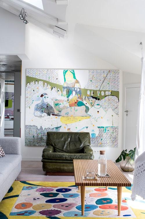 Stor konst i vardagsrummet med målning av Per Enoksson. Vintage läderfåtölj, design Arne Norell, 60-talsbord från NK, som Oliver ärvt av sin gudfar.