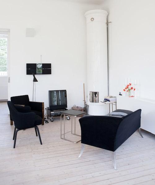 Kakelugnen från 1925 är en skön samlingspunkt under kulna kvällar. Soffa från Källemo i design av Alice Kunftova. Fåtöljen ritad av Saarinen.