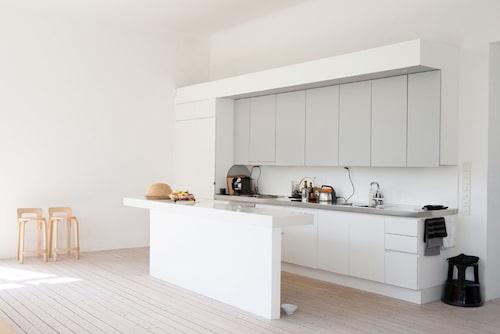 Den ljusa köksinredningen från finska Saari kompletterades med en platsbyggd bänk som tillåter köksarbete med utsikt genom de höga skolfönstren. Barpallarn av Alvar Aalto.