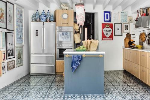 Även i köket har man unnat sig väggar med konst, foton och minnen. Inredning i ek från Ikea.