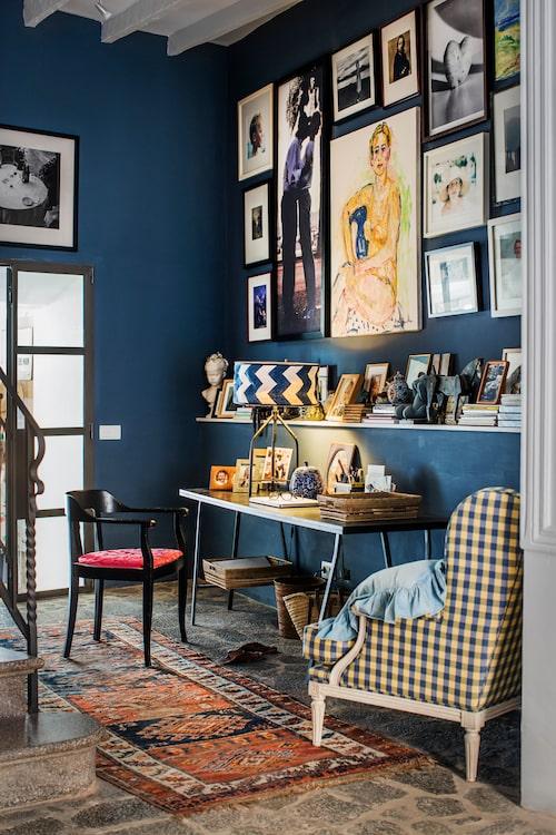 Tavelväggen med foton och minnen är viktig för familjen och skapar en hemtrevlig och välkomnande atmosfär i receptionen, tillika familjens kontor.