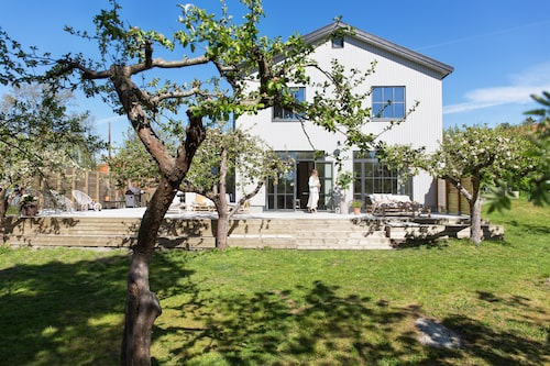 Trädgården har gott om livskraftiga öppelträd. Årets stora projekt är att anlägga blomsterbäddar. Den 100 kvadratmeter stora, nybyggda altanen som löper runt en kort- och en långsida av huset har sol hela dagen.