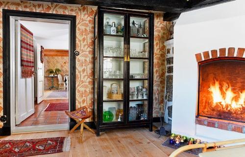 Vy från vardagsrummet via hallen in i matrummet på motstående sida. Skåpet från Lauritz.com rymmer samlingen av porslin och glas, trebent pall från Läkarmissionen och matta från Ikea. Öppna spisen målades om för att bli fin igen.