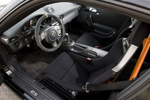 Porschekupén är luftig i jämförelse. Den mockaklädda ratten har mittmarkering i gult. Skalstolar i kolfiber. AC saknas.