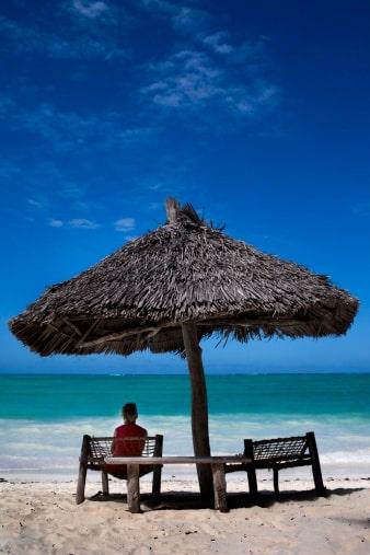 En turist tar igen sig under ett av strandens parasoller.
