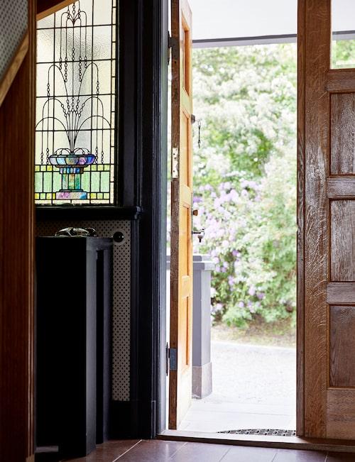Entrén pryds av ett tidstypiskt blyinfattat fönster.