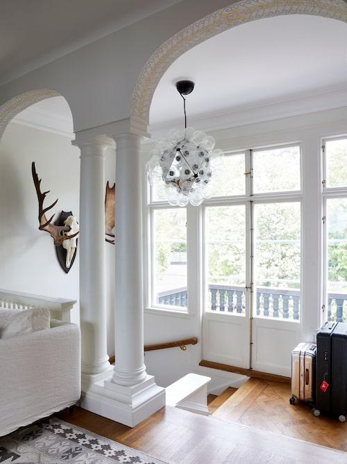 Stilmässigt har huset inslag av både jugend och nationalromantik, men här finns också klassicistiska inslag med pelare och valv. I vardagsrummet på övre planet ligger den vackra originalparketten. Väggarna är målade i en beigegrå ton. I taket en lampa från Flos. Och på väggen en jakttrofé, en enorm älg som André har fällt.
