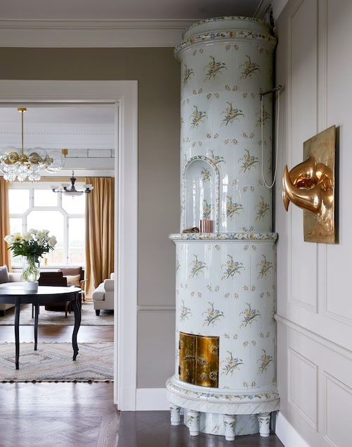 Kakelugnen med sirligt rar blomdekor står i skarp kontrast mot konstverket på väggen, köpt på Bukowskis.