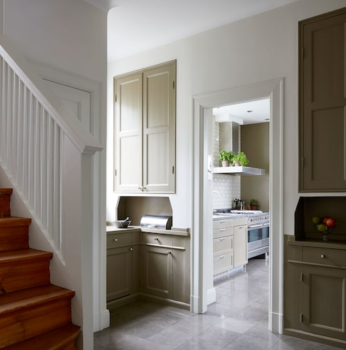 För att nå köket passerar man genom den fantastiska serveringsgången. Färgen på luckorna är densamma som köksväggens, Mouses back från Farrow & Ball. Stengolvet löper från hallen in i köket.