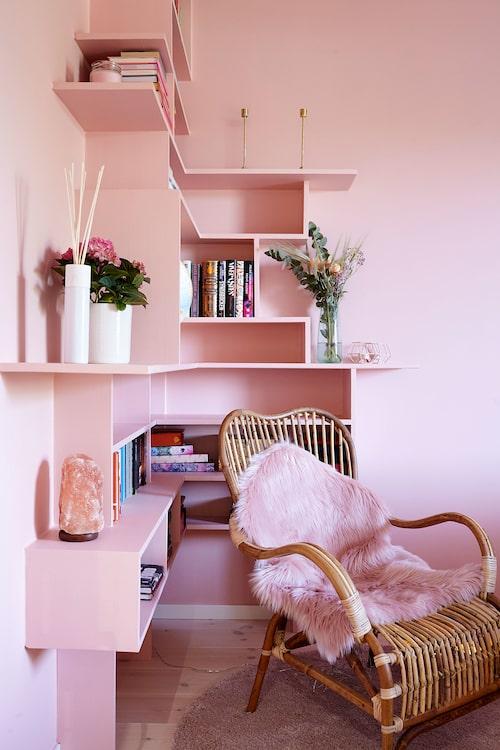 """Platsbyggd bokhylla målad i samma färg som resten av sovrummet. Bambufåtölj och fuskfårskinn, båda från Jysk. """"Jag har en del salt och kristaller i sovrummet som sägs vara bra för hjärtchakrat. Det kan låta flummigt, men jag tänker att det kan ju inte skada, så jag testar i alla fall!"""""""