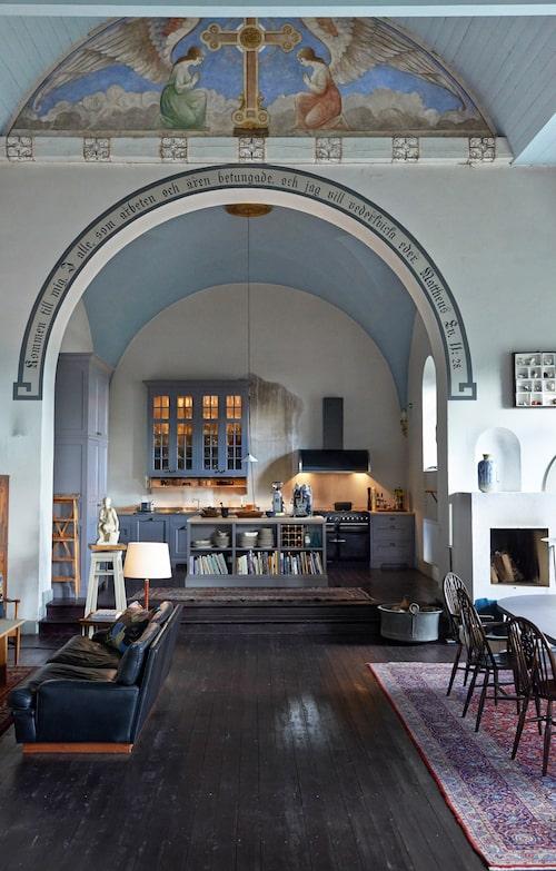 Köket fick en självklar placering längst fram i det tidigare koret. I dag intar köksön altarets gamla plats. Kyrkans takmålningar är original och går i en gråblå färgskala.