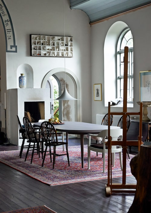 Mattor och bord är arv från Jans barndomshem, stolarna är av engelsk windsormodell och taklampa Semi från Gubi. Dörren leder ut till trädgården där en tupp och några höns fritt strövar omkring. På väggen ett verk av konstnären Lars Peterson.