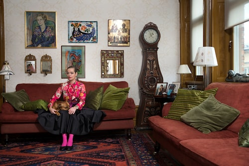 Stiloraklet Camilla i egendesignad kjol och blus och örhängen inköpta i New Delhi. På väggen ovanför syns bland annat ett porträtt av Thulins farmor från 1940-talet, en rysk ikonmålning och glasmålningar inköpta i turkiska Bodrum där paret Thulin-Rabaeus bor delar av året.