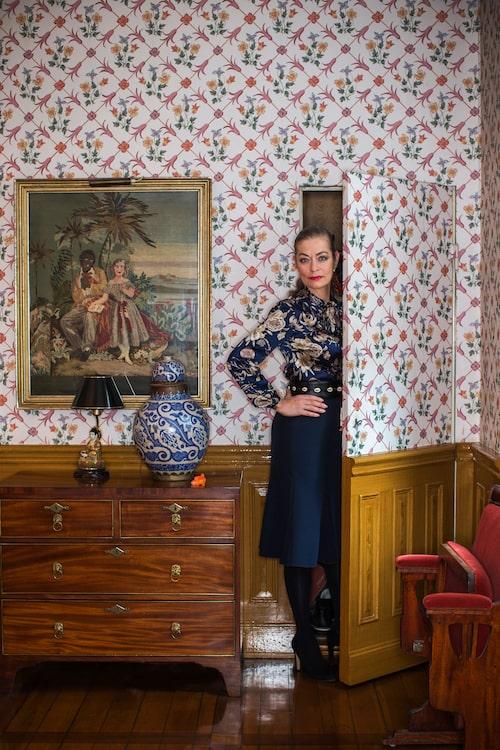 """""""Om jag inte klär mig i folklore eller antika kläder så är det alltid min egen design som gäller"""", säger Camilla Thulin. Ovanpå Chippendalebyrån står en orientalisk urna. Tavlan i guldram på väggen är från 1870, broderad av en släkting."""