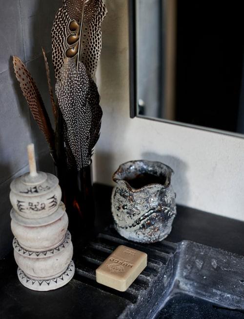 Några vackra fjädrar i brun glasvas gläder ögat, liksom förvaringsasken med balinesisk touch och den krackelerade vasen, båda Love warriors.