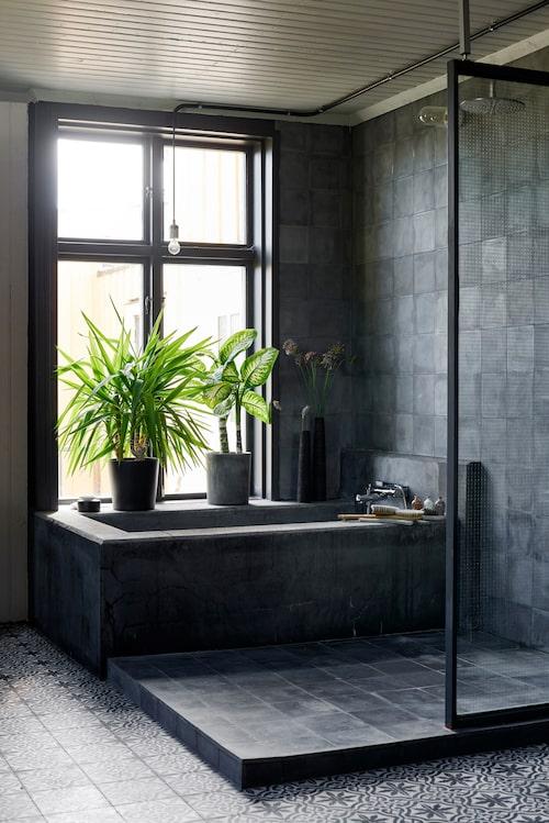Dusch- och badhörnan med platsgjutet badkar i betong och inglasat parti. En klack av matt mörkgrått kakel är lagt runt badkaret för att skapa lite högre nivå. Blandare från Tapwell.