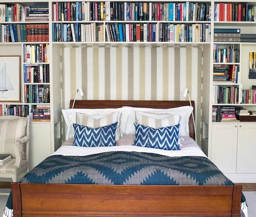 Sängramen från La Grange har funnits med länge. Den är anpassad för att rymmas i den platsbyggda hyllan som ramar in hela härligheten. På väggen ett tyg, detsamma som i kuddarna på sängen. Pläden är köpt i Laos. Nattduksborden är infällda som små nischeri hyllan, smart och platsbesparande.
