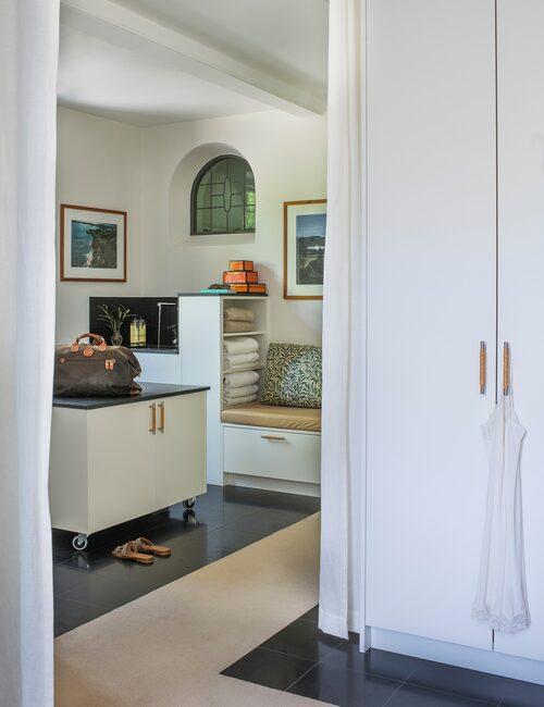 Mellan badrum och dressingroom bildar den nedsänkta ljusa heltäckningsmattan en mjuk gång i stengolvet. Garderober från Kvänum, med lindade läderhandtag. Den hjulförsedda bänken är familjens bästa tips: här döljs resväskor, och platsen blir perfekt att packa ner och upp på, och för tvätta alla kläder, i samma rum. Platsbyggd bänk, och intill den en vask för avsköljning av golfklubborna.
