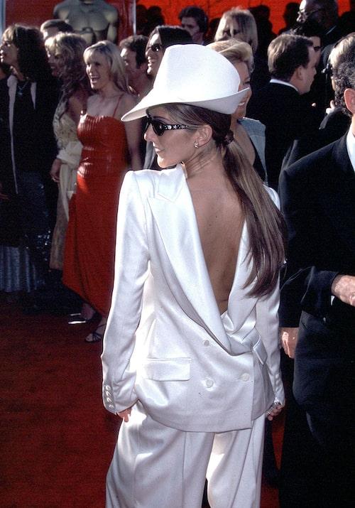 Céline Dion i bak och fram-vänd smoking på röda mattan.