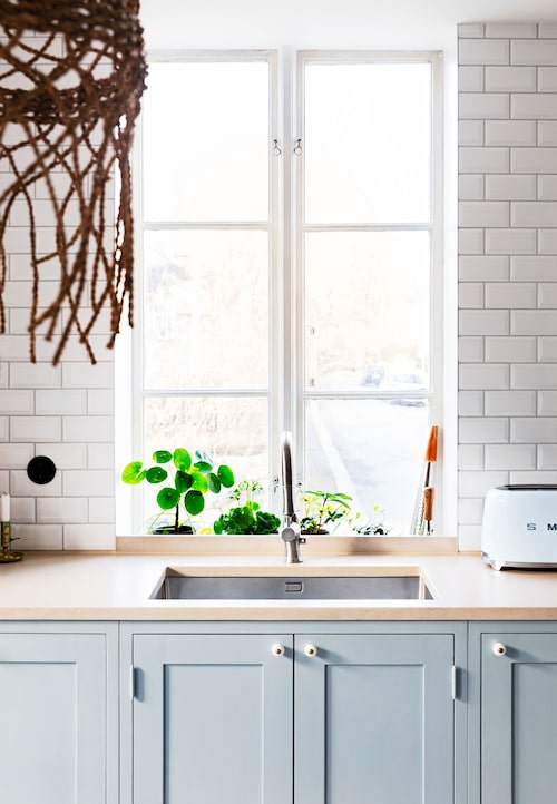 """""""Det bästa är att vi har diskbänken vid fönstret!"""" Knopparna i emalj och mässing kommer från Byggfabriken i Göteborg."""