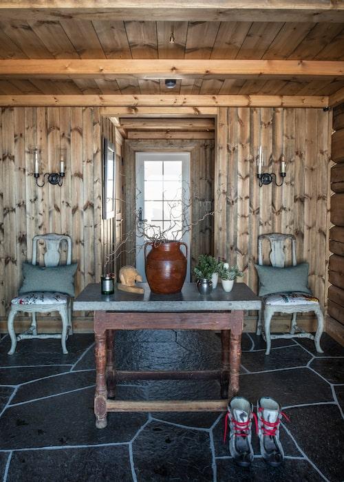 Hallen har ett vackert golv av skiffer från norska Otta. Fogen är gjord efter ett gammalt recept för att inte se för perfekt ut. Dekorationerna på det gamla bordet med kalkstensskiva byts ut efter årstiden. Vägglampor, Vaughan.